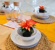 Τεχνητές εγκαταστάσεις με τα πορτοκαλιά λουλούδια στον πίνακα Dinning Στοκ Εικόνες