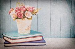 Τεχνητός αυξήθηκε στο δοχείο λουλουδιών με το σωρό των σημειωματάριων Στοκ φωτογραφία με δικαίωμα ελεύθερης χρήσης