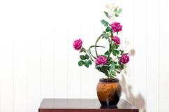 τεχνητός αυξήθηκε Floral βάζο λουλουδιών ανθοδεσμών στον ξύλινο πίνακα στο whi Στοκ Φωτογραφίες