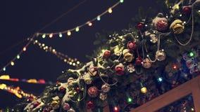 Τεχνητός κλάδος του FIR με τις χάντρες και τις σφαίρες Χριστουγέννων στη στέγη σπιτιών απόθεμα βίντεο