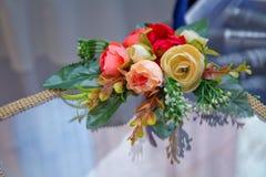Τεχνητός κόκκινος, κίτρινος αυξήθηκε ανθοδέσμη Διακοσμητικό υπόβαθρο τεχνητών λουλουδιών Στοκ Φωτογραφία