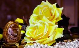 Τεχνητό καφετί αυγό Πάσχας και τεχνητά κίτρινα τριαντάφυλλα στοκ φωτογραφία με δικαίωμα ελεύθερης χρήσης