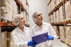 Τεχνικοί γυναικών στην αποθήκη εμπορευμάτων εργοστασίων παγωτού Στοκ φωτογραφίες με δικαίωμα ελεύθερης χρήσης