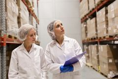 Τεχνικοί γυναικών στην αποθήκη εμπορευμάτων εργοστασίων παγωτού Στοκ Φωτογραφία