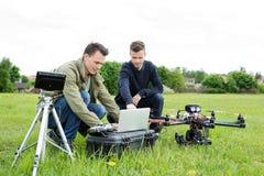Τεχνικοί που χρησιμοποιούν το lap-top με το τρίποδο και UAV στοκ εικόνες