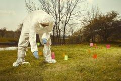 Τεχνικός εγκληματολόγων στην αποστειρωμένη προστατευτική γενική εργασία DNA στην επισήμανση των στοιχείων στην έκταση με τις σημα στοκ εικόνα με δικαίωμα ελεύθερης χρήσης