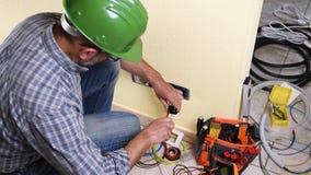 Τεχνικός ηλεκτρολόγων στην εργασία για ένα κατοικημένο ηλεκτρικό σύστημα Οικοδομική Βιομηχανία απόθεμα βίντεο