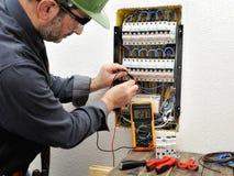 Τεχνικός ηλεκτρολόγων στην εργασία με το προστατευτικό κράνος σε ένα resid Στοκ Εικόνες