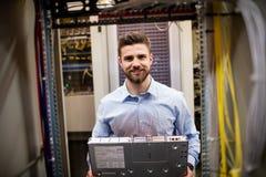 Τεχνικός που αφαιρεί τον κεντρικό υπολογιστή από τοποθετημένο το ράφι κεντρικό υπολογιστή Στοκ Εικόνα