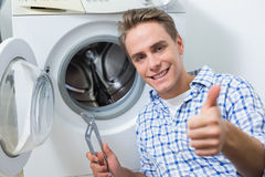 Τεχνικός που επισκευάζει το πλυντήριο ενώ φυλλομετρεί επάνω Στοκ Φωτογραφίες