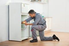 Τεχνικός που ελέγχει το ψυγείο με το ψηφιακό πολύμετρο στοκ εικόνα με δικαίωμα ελεύθερης χρήσης