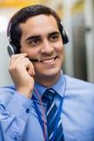 Τεχνικός που μιλά στα επικεφαλής τηλέφωνα Στοκ φωτογραφία με δικαίωμα ελεύθερης χρήσης
