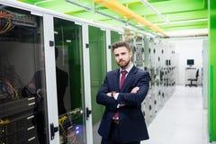 Τεχνικός που στέκεται με τα όπλα που διασχίζονται σε ένα δωμάτιο κεντρικών υπολογιστών Στοκ Φωτογραφίες