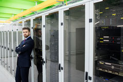Τεχνικός που στέκεται με τα όπλα που διασχίζονται σε ένα δωμάτιο κεντρικών υπολογιστών Στοκ φωτογραφία με δικαίωμα ελεύθερης χρήσης