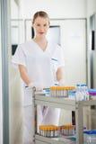 Τεχνικός που ωθεί το ιατρικό κάρρο στο νοσοκομείο Στοκ Φωτογραφίες