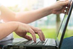 Τεχνολογία και επικοινωνία, εργασία στο πληκτρολόγιο με ένα lap-top υπαίθρια, στοκ εικόνες