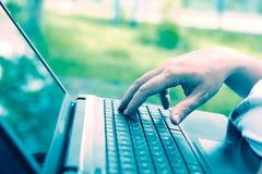 Τεχνολογία και επικοινωνία, εργασία στο πληκτρολόγιο με ένα lap-top υπαίθρια, στοκ εικόνα