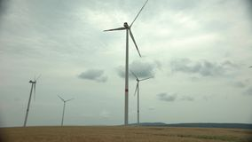 Τεχνολογία πάρκων αέρα pinwheels σε ένα cornfield γεωργίας τοπίο με το νεφελώδη ουρανό φιλμ μικρού μήκους