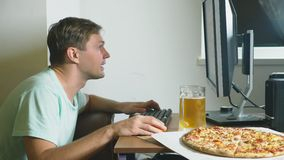 Τεχνολογία, παιχνίδια, ψυχαγωγία, παιχνίδι και έννοια ανθρώπων ένας νεαρός άνδρας που παίζει ένα παιχνίδι στον υπολογιστή στο σπί απόθεμα βίντεο