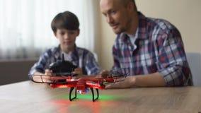 Τεχνολογικό παιχνίδι υψηλών σημείων, μικρό παιδί που λειτουργεί quadcopter στο σπίτι, έχοντας τη διασκέδαση απόθεμα βίντεο