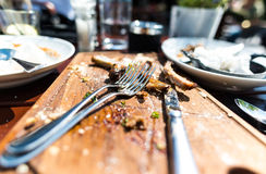 Τελειωμένο μεσημεριανό γεύμα μπριζολών με τα μαχαιροπήρουνα Στοκ Εικόνες
