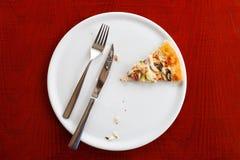 Τελευταίο κομμάτι της πίτσας σε ένα άσπρο πιάτο Ξύλινα επιτραπέζια μαχαίρι και δίκρανο στοκ εικόνες