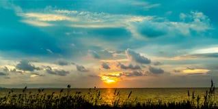 τελευταίο φως του ηλιοβασιλέματος πανοράματος στη γραμμή οριζόντων πέρα από τη θάλασσα και το γυαλί Στοκ Εικόνες