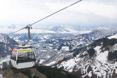 Τελεφερίκ στην κορυφή της κάλυψης βουνών με το χιόνι στοκ εικόνα