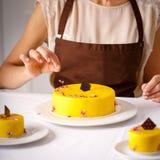 Τελικός καλλωπισμός του μεγάλου κίτρινου κέικ Στοκ φωτογραφία με δικαίωμα ελεύθερης χρήσης