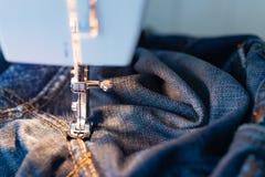 Τζιν επισκευής στη ράβοντας μηχανή Άποψη του υφάσματος, της βελόνας και του νήματος Φωτισμός από τον ενσωματωμένο πυρακτωμένο λαμ στοκ εικόνα