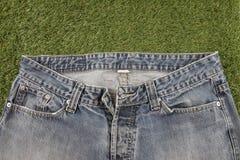 Τζιν παντελόνι σε ένα τεχνητό υπόβαθρο χλόης Στοκ Εικόνες