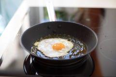 Τηγάνισμα αυγών στο καυτό πετρέλαιο στοκ φωτογραφία