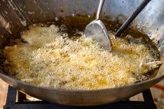 Τηγάνισμα τηγανισμένου taro με το βατραχοπέδιλο στο βράζοντας πετρέλαιο στο τηγάνι στοκ φωτογραφίες