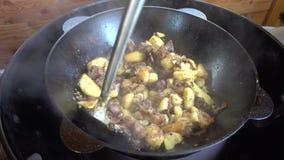 Τηγάνισμα των πατατών με το κρέας, τα κρεμμύδια και τις ντομάτες kazan σε μια σχάρα αερίου απόθεμα βίντεο