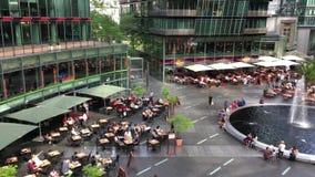 Τηγάνι πέρα από τους ανθρώπους που απολαμβάνουν τα εστιατόρια και τις υπηρεσίες στο κέντρο Potsdamer Platz Sony απόθεμα βίντεο