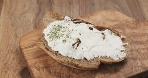 Τηγάνι σε αργή κίνηση της πτώσης arugula στο χωριάτικο ψωμί με το τυρί ricotta Στοκ Φωτογραφίες
