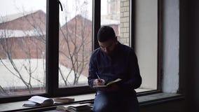 Τηγάνι του νεαρού άνδρα που μελετά τη συνεδρίαση στο windowsill φιλμ μικρού μήκους