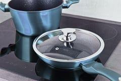 Τηγανίζοντας δοχείο τηγανιών και χάλυβα στη σύγχρονη επαγωγή cooktop στοκ εικόνες