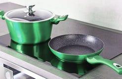 Τηγανίζοντας δοχείο τηγανιών και χάλυβα στη σύγχρονη επαγωγή cooktop στοκ εικόνα