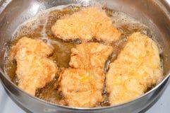 Τηγανίζοντας κρέας στο καυτό πετρέλαιο σε ένα τηγανίζοντας τηγάνι Στοκ Φωτογραφία