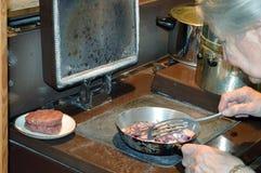Τηγανίζοντας κρεμμύδια, που προετοιμάζουν ένα γεύμα της μπριζόλας λωρίδων Στοκ Φωτογραφία