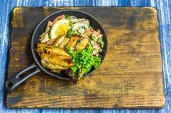 Τηγανίζοντας τηγάνι με τα ψάρια, το λεμόνι και τα χορτάρια Στοκ Εικόνα