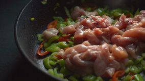 Τηγανίζοντας τηγάνι με την κινηματογράφηση σε πρώτο πλάνο πιπεριών και κομματιών κοτόπουλου βίντεο απόθεμα βίντεο