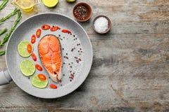 Τηγανίζοντας τηγάνι με τις φέτες του λεμονιού, του πιπεριού και του σολομού Στοκ Εικόνα
