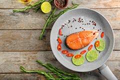 Τηγανίζοντας τηγάνι με τις φέτες του λεμονιού, του πιπεριού και του σολομού Στοκ Εικόνες