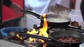 Τηγανίζοντας τηγάνι στην πυρκαγιά, τηγανίζοντας λαχανικά αρχιμαγείρων στην πυρκαγιά που ρίχνει τους σε ένα τηγανίζοντας τηγάνι απόθεμα βίντεο