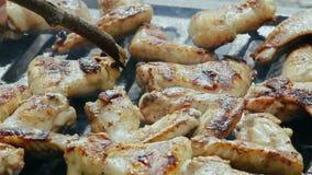 Τηγανίζοντας φτερό κοτόπουλου που καπνίζεται σε μια σχάρα και που αναποδογυρίζεται ενώ cookin φιλμ μικρού μήκους
