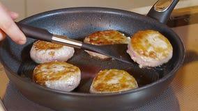 Τηγανίζοντας Cutlets κοτόπουλου ατόμων στο τηγάνισμα του τηγανιού απόθεμα βίντεο