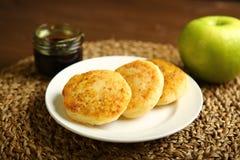 Τηγανίτα τυριών σε ένα πιάτο με το μέλι και το μήλο Στοκ Φωτογραφία