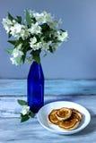 Τηγανίτες για το brekfast κοντά στα όμορφα άσπρα λουλούδια Στοκ εικόνα με δικαίωμα ελεύθερης χρήσης